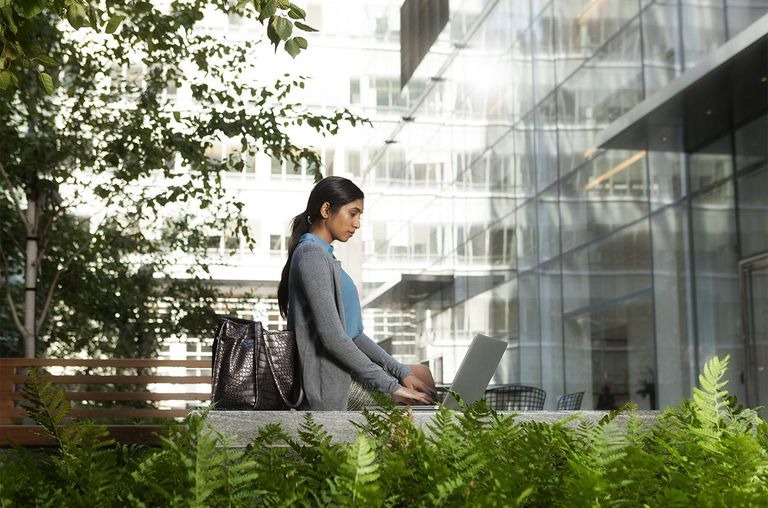 Woman working on computer outside office