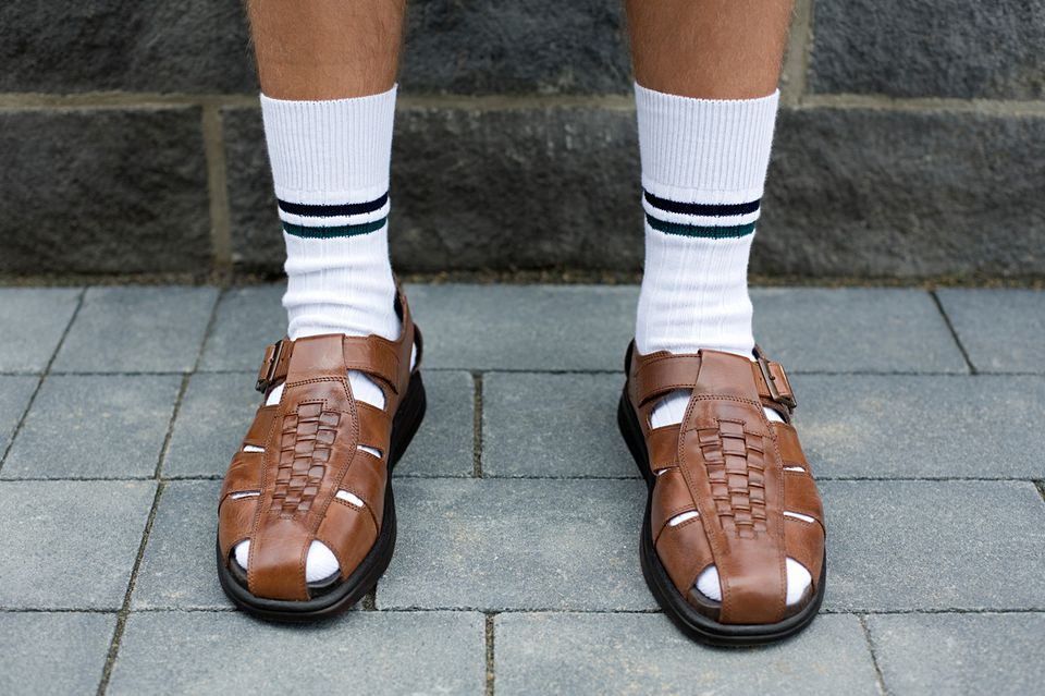 Man wearing socks in sandals.