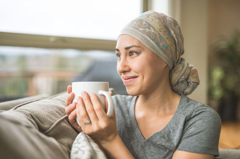 Woman with cancer sitting on couch with a mug