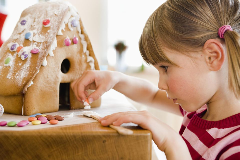 Little girl making a gingerbread house