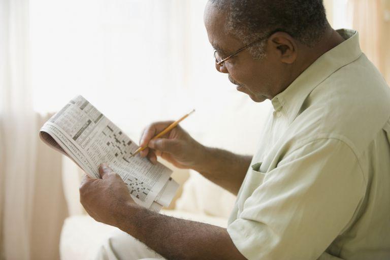 senior man doing crossword puzzle