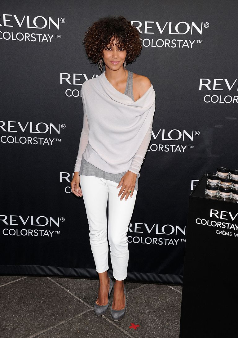Halle Berry, dressed in cropped white jeans, grey shoes, and gray tops.