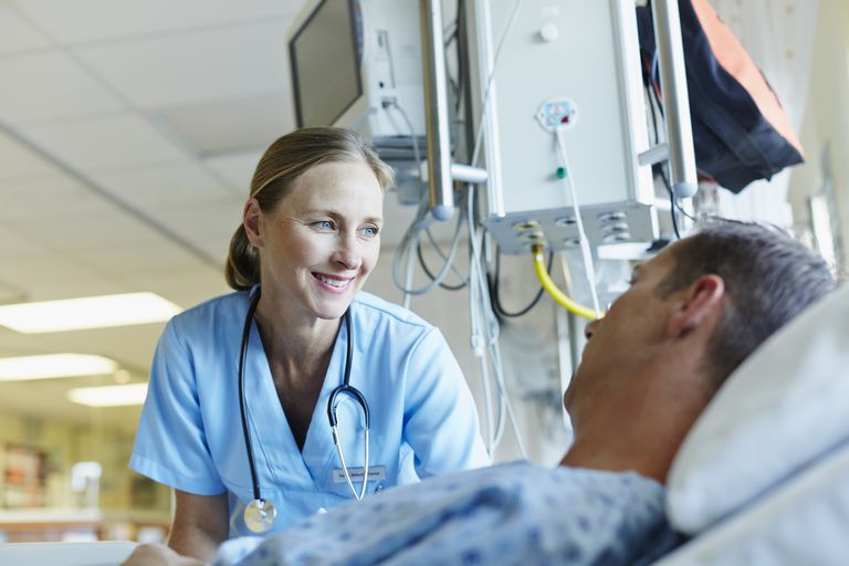 Smiling doctor looking at patient in hospital ward
