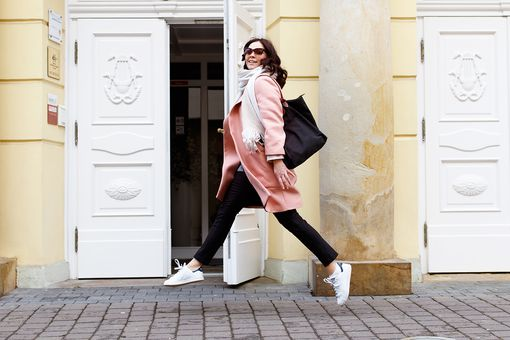 Woman wearing black jeans and pink coat jumping