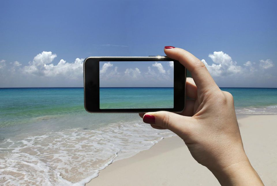 Woman photographing a beach with i-phone