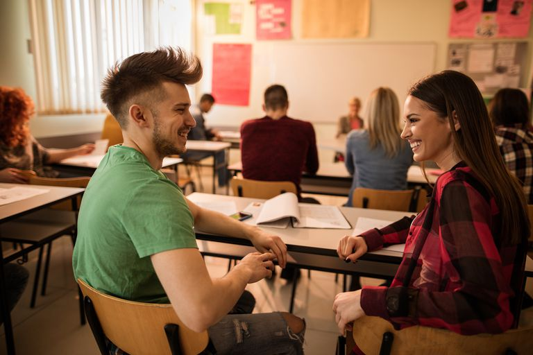Two happy students talking to each other in the classroom.