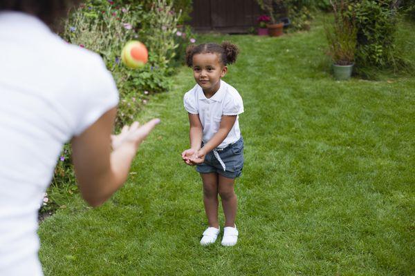 Preschooler girl playing ball outside