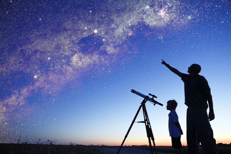 Man showing milky way to little boy,
