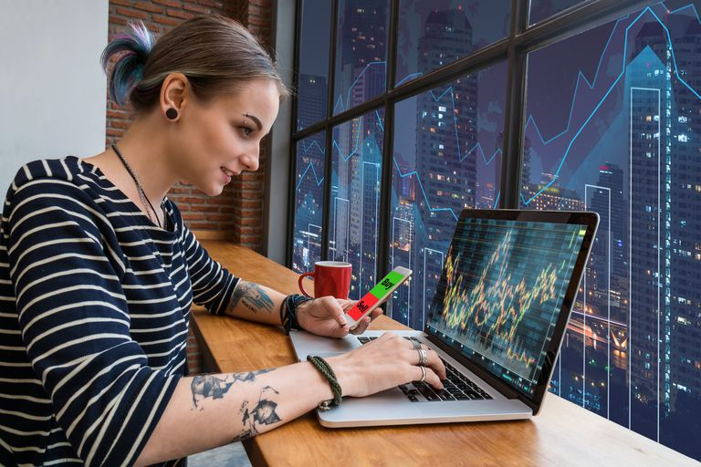 Business financial and forex concept, Hipster young Woman freelancer using the technology laptop and smart phone mobile showing trading graph with the stock exchange trading graph screen background
