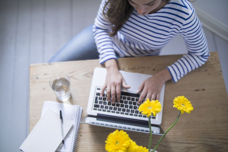 Woman on computer with yellow flowers and water on table.