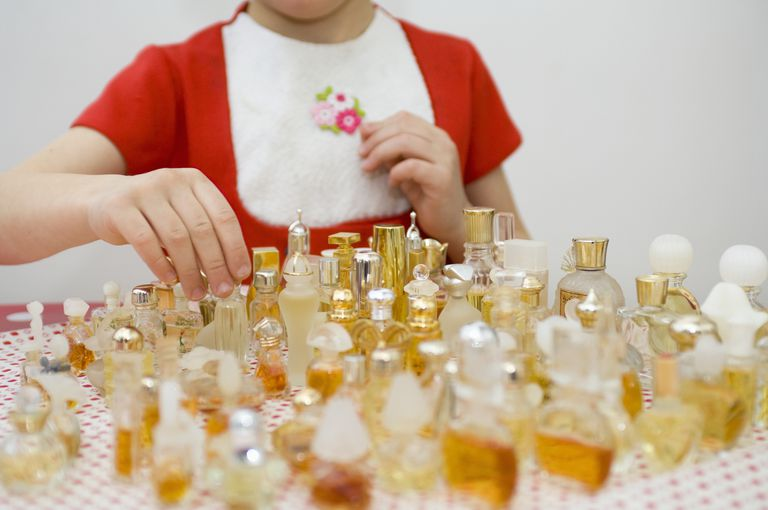 girl playing with perfume collection