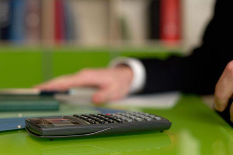 Businessman at desktop with calculator