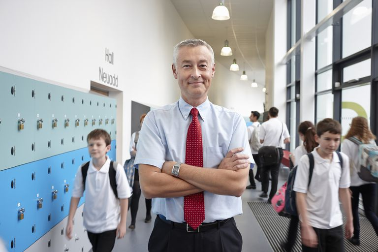 Portrait of male teacher with arms folded in school corridor