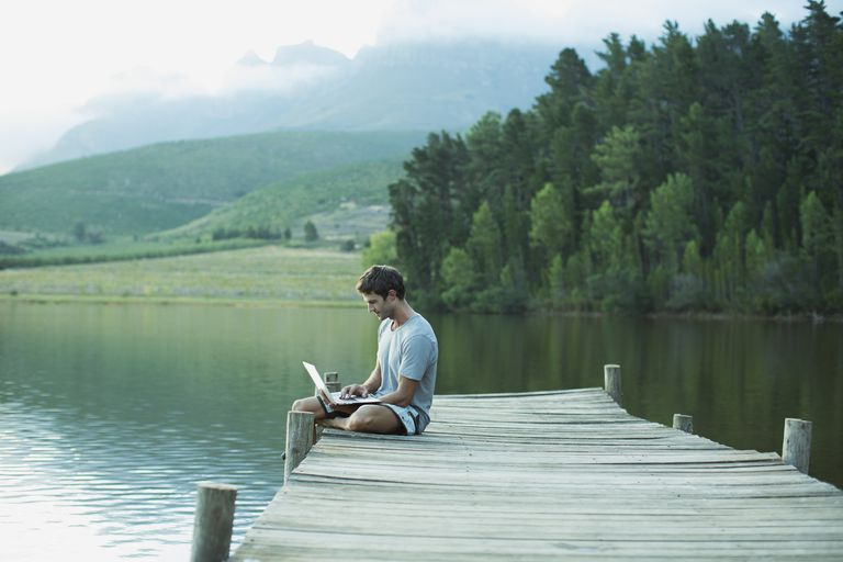 Man using laptop on dock over calm lake