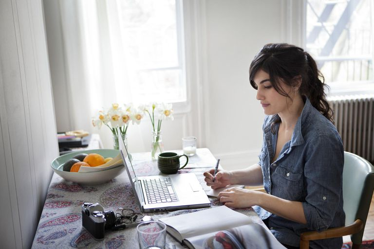 Young Woman Writing by Computer in Apartment