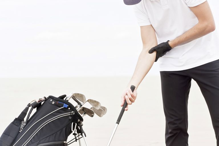 Photo of a golfer holding his elbow.
