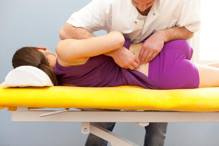 Photo of PT moblizing a patient's spine.
