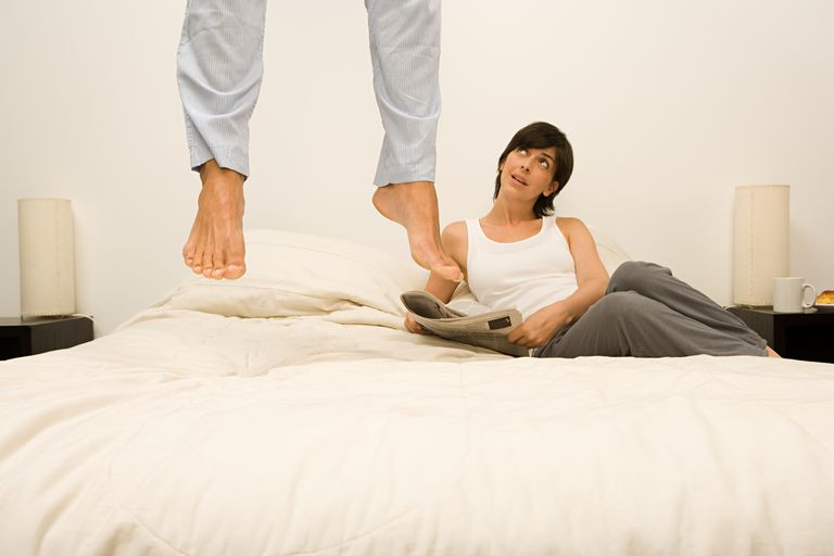 man jumping on bed while woman lying on bed watches.