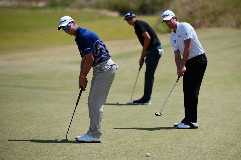 John Senden (L) of Australia putts alongside two other golfers during a practice round prior to the start of the 2015 U.S. Open