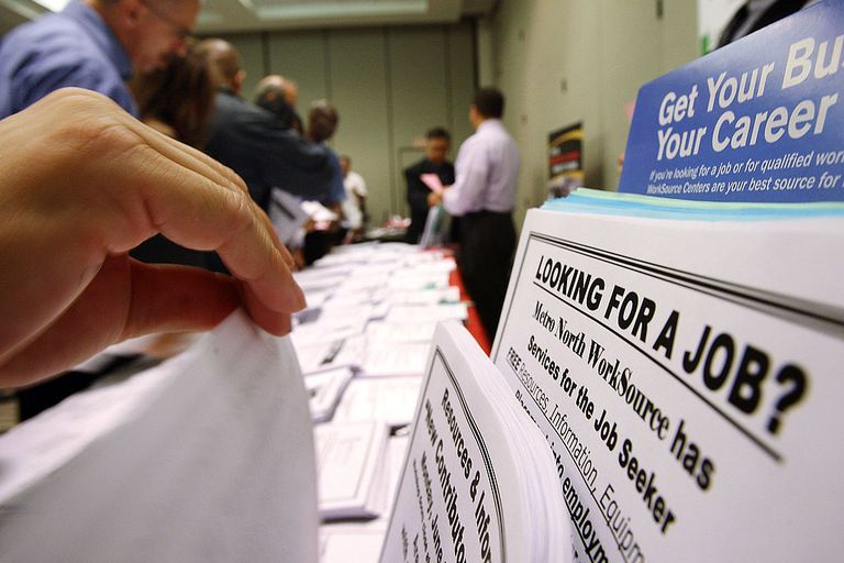 person thumbing through job search paperwork at job fair