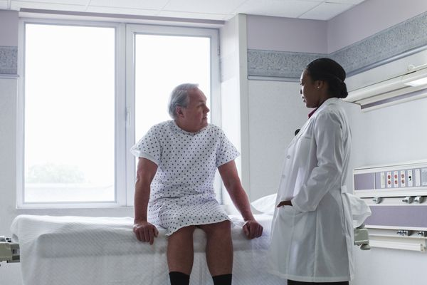 Woman doctor talking to patient in hospital