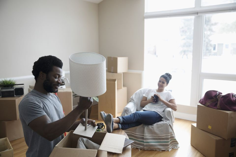man packing lamp, moving out of home
