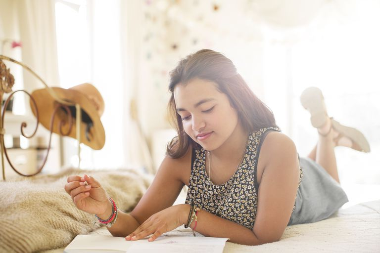 Teenage girl lying on bed and writing in notebook