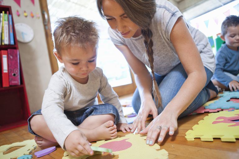 Adult care provider playing with child on floor.