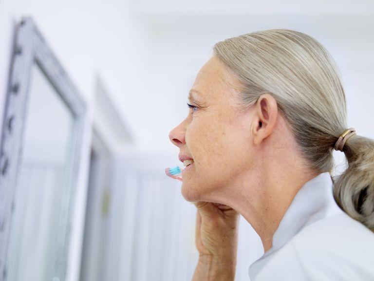 senior woman brushing teeth