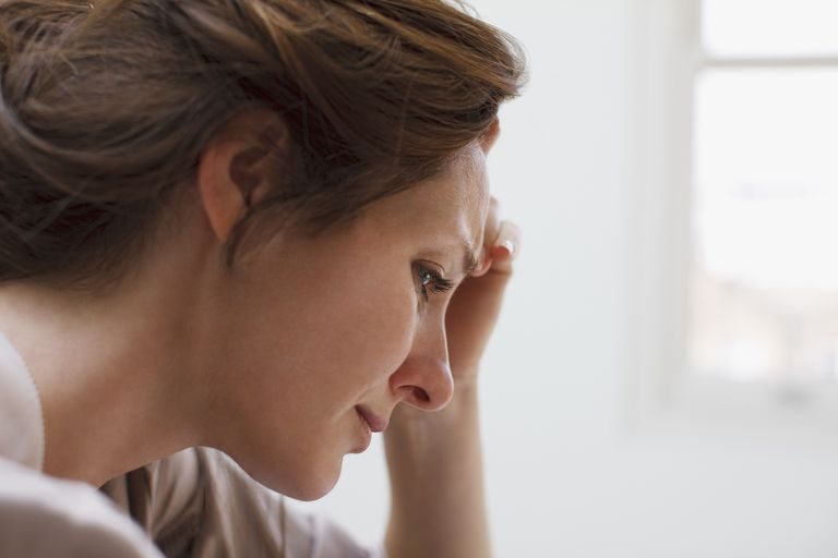 Woman holding her head with her hand looking sad