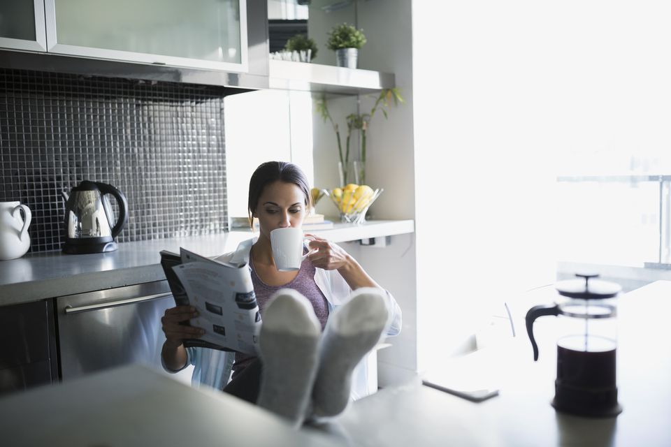 Woman drinking coffee reading magazine with feet up