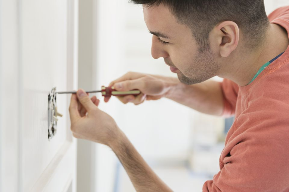 Young man installing light switch at home