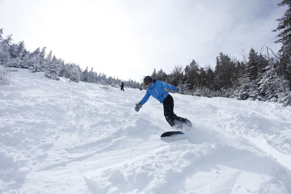 A female snowboarder carves in fresh snow in New Hampshire.