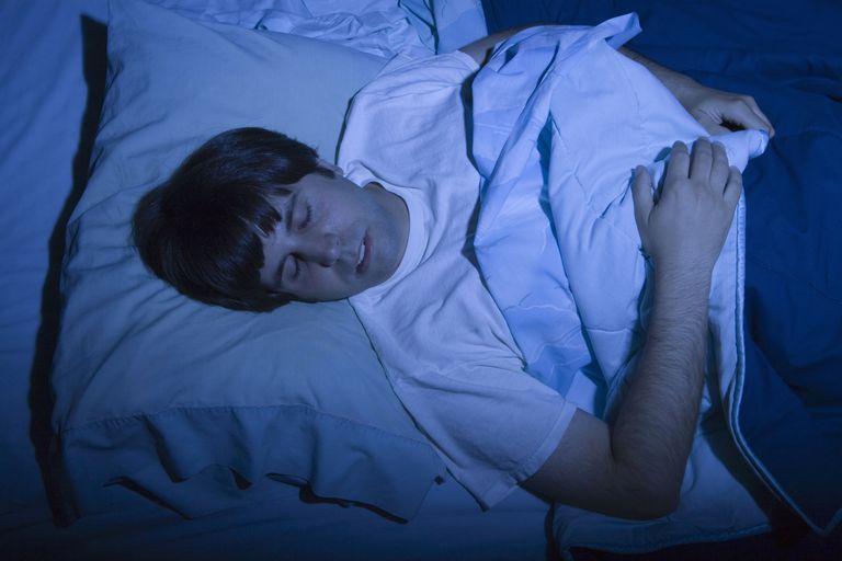 man in dark room sleeping