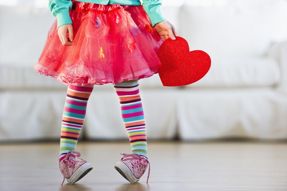 Young girl wearing colorful tights and holding paper heart