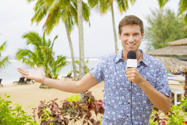 A photo of a reporter holding a microphone at the beach.