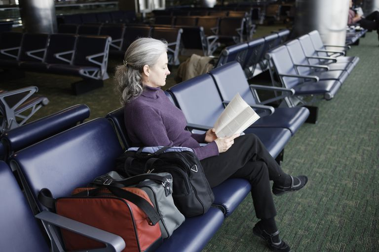 Woman reading in airport terminal