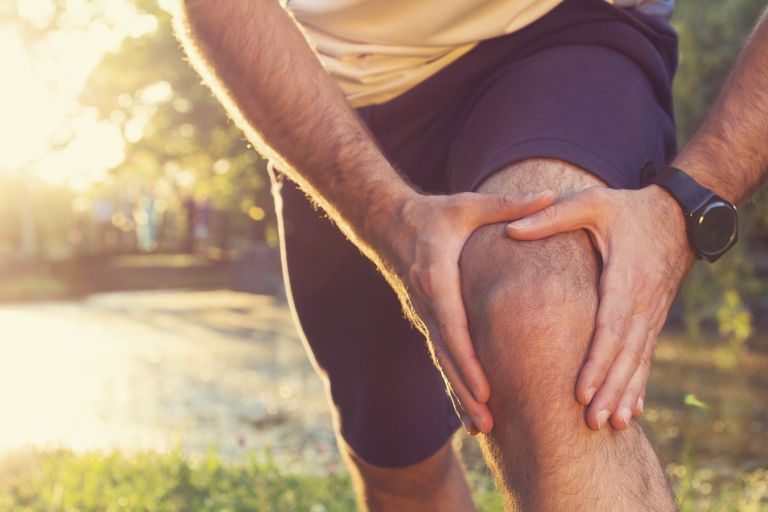 man holding a painful knee