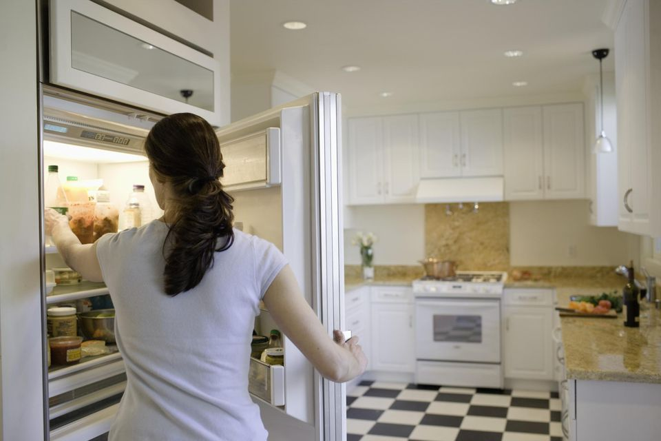 Woman reaching into refrigerator, rear view