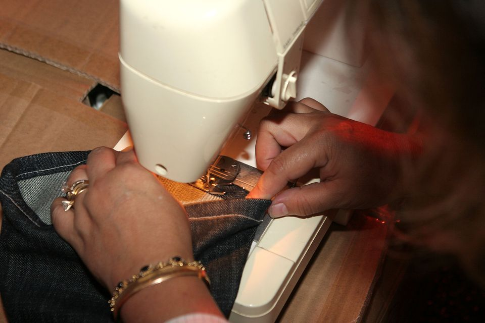 A woman fixing the hem of pair of slacks