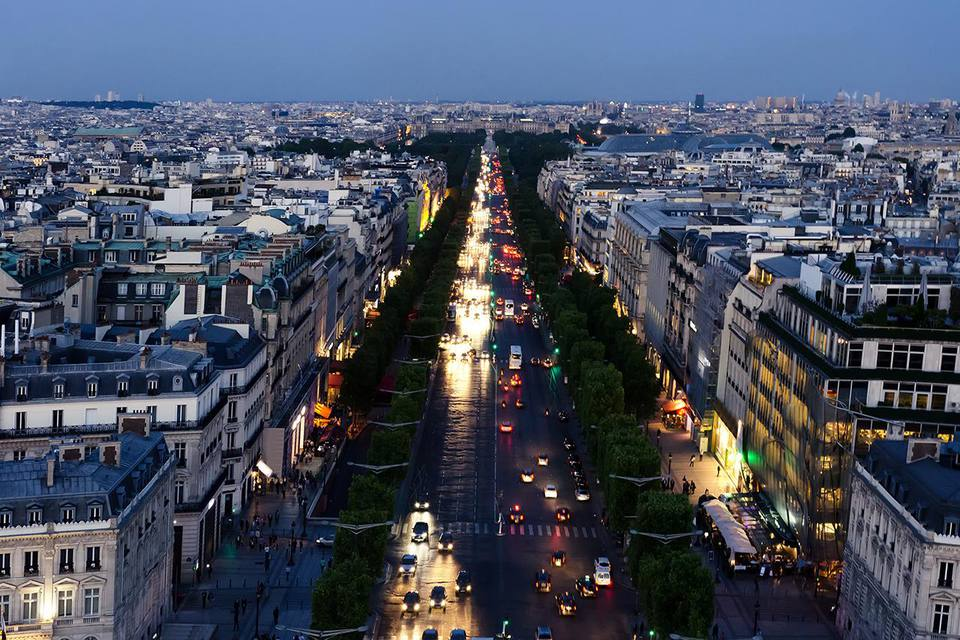 Cityscape of Paris in dusk with skyline and cars on street in France.