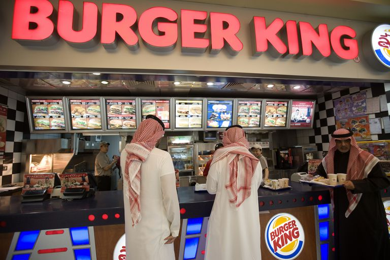 Two Saudi tourists and a Kuwaiti eating at Burger King, Kuwait City.