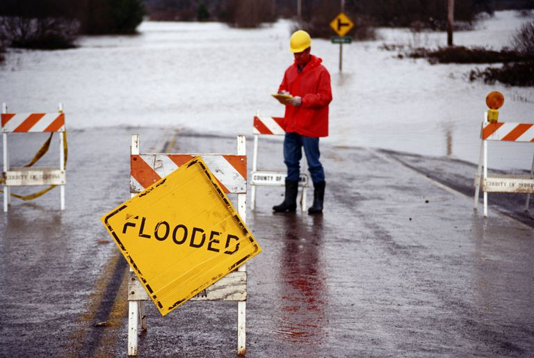 Man in orange jacket standing next to flooded area near