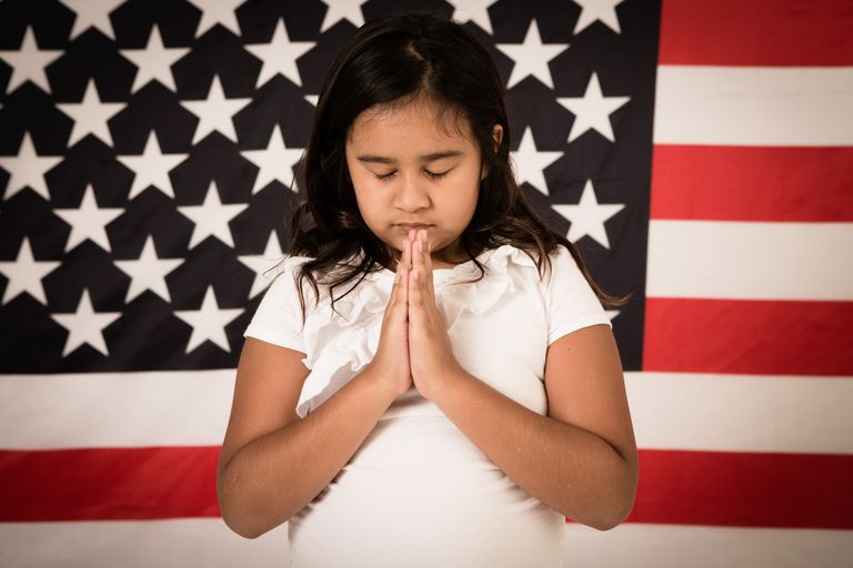 Young Christian Girl Praying in Front of American Flag