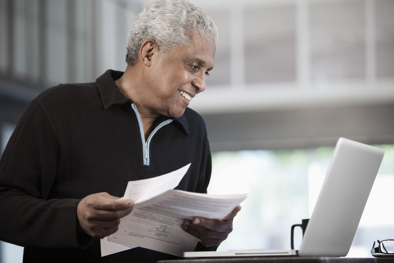 Black man holding paperwork and using laptop
