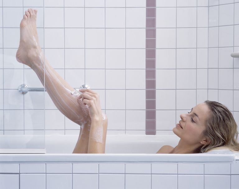 Woman Shaving Legs in Bath