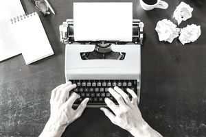 Close-up of man using typewriter with crumpled paper on desk