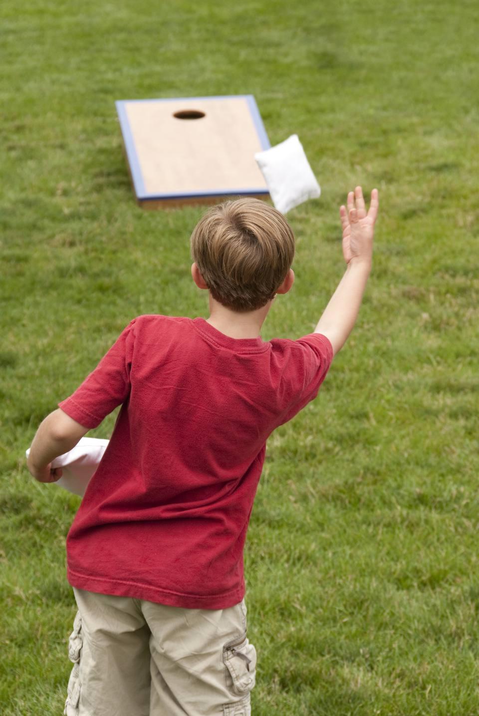 Young boy playing Cornhole