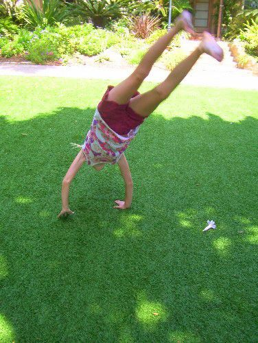 girl doing cartwheel on synthetic turf