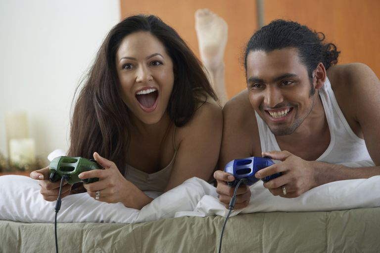 Couple laying on bed playing video games